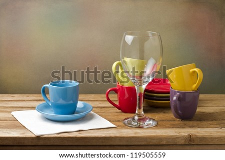 Still life with colorful tableware on wooden table over grunge background - stock photo