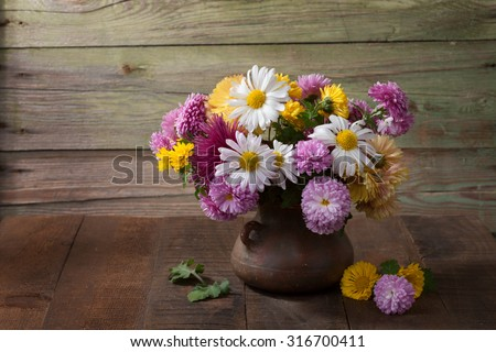 Still life with colourful chrysanthemums bunch on old wooden table - stock photo