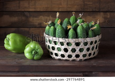 Still life with cucumbers. Cucumbers in a basket on a wooden table. - stock photo