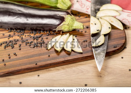 still life with cutted eggplant slices, kitchen knife - stock photo