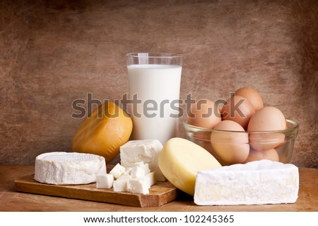 still life with dairy products, milk, cheese and eggs on a wooden background - stock photo