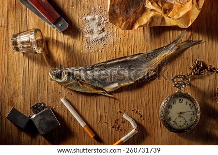 Still life with dried fish, cigarettes and a clock on a chain