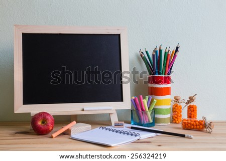 Still life with empty blackboard and colored chalks on wooden table over wall grunge background - stock photo