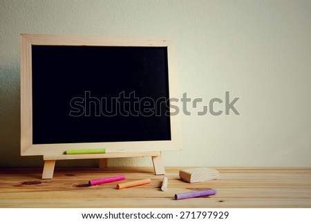 Still life with empty blackboard and colored chalks on wooden table over wall grunge background