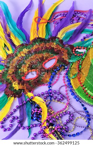 Still life with feathered mask, shiny party top hat,  beads on purple background. Objects symbolize Mardi Gras and also New Years, the opera, carnivals and the arts. - stock photo
