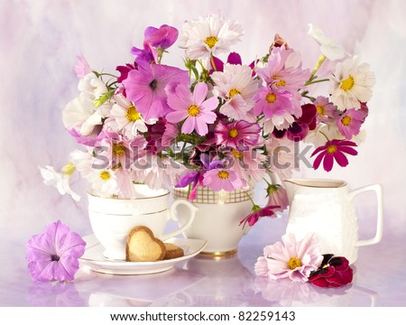 still life with flowers and a cup of kosmeya - stock photo