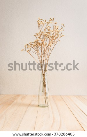 Still life with flowers in glass bottle on wooden table - stock photo