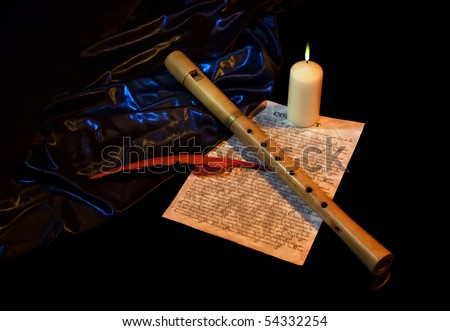 Still Life with flute, burning candle, manuscript and red feather - stock photo