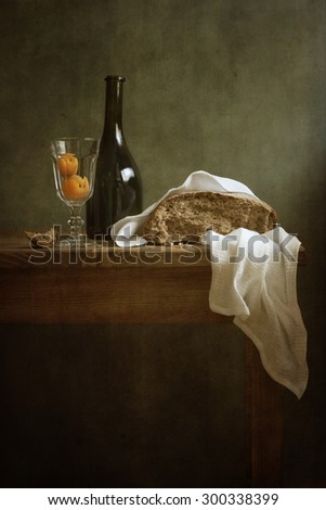 Still life with fresh bread and a bottle of wine - stock photo