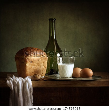 Still life with fresh bread, milk, eggs and a bottle of wine - stock photo