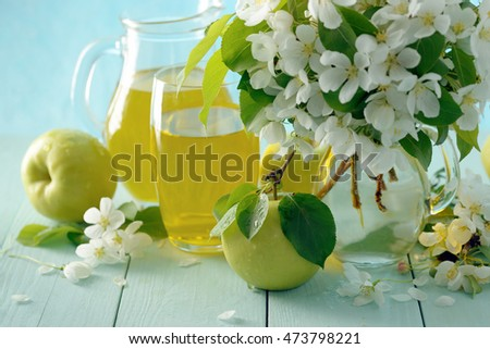 Still life with fresh juice, juicy green apples and bunch of flowers on sky blue background.