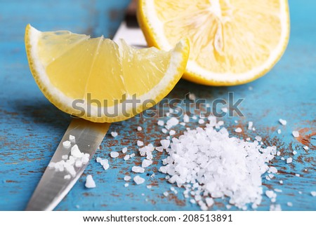 Still life with fresh lemon, knife and salt on old wooden table - stock photo