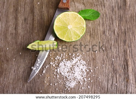 Still life with fresh lime, knife and salt on old wooden table - stock photo