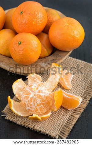 Still life with fresh mandarins in a wooden basket - stock photo