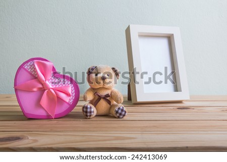 Still life with gift box on wooden table over grunge background, Valentine concept - stock photo