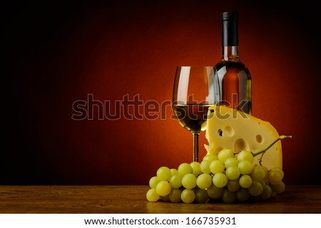 still life with glass and bottle of white wine, cheese and grapes - stock photo