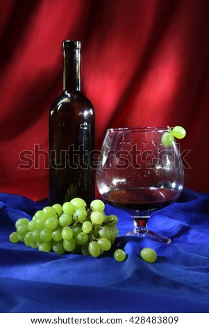 Still life with glass of good red wine and bunch of grapes - stock photo