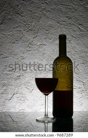Still-life with glass of red wine and bottle - stock photo