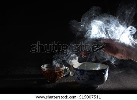 Still life with glass teacup and bowl and steam. Hand which hold up a sticks under ornate bowl.
