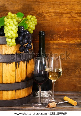 Still life with glasses of the red and white wine and barrel