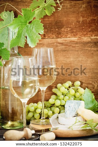 Still life with glasses of white wine, bottle and chesse