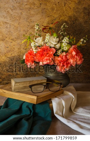 Still life with glasses resting on the book and  flower in a vase.