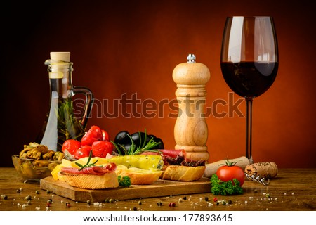 still life with gourmet mediterranean snacks and glass of red wine