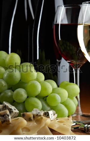 still life with grape, cheese and wine on the black background - stock photo