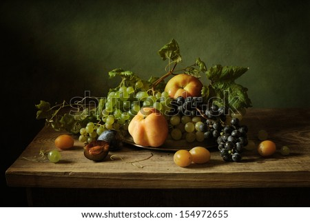 Still life with grapes, apples and plums - stock photo