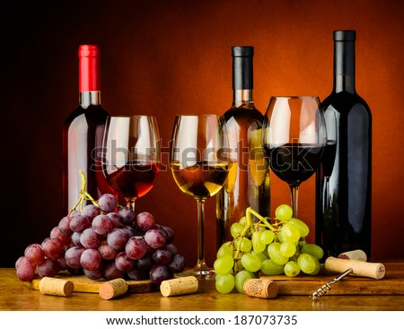 still life with grapes, red, white and rose wine - stock photo