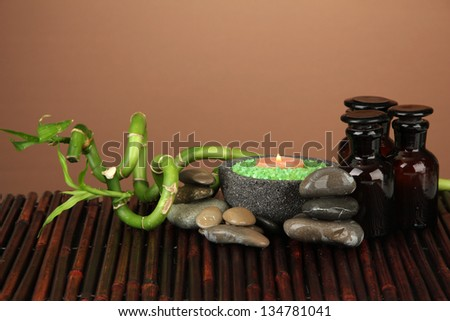 Still life with green bamboo plant and stones, on bamboo mat on color background - stock photo