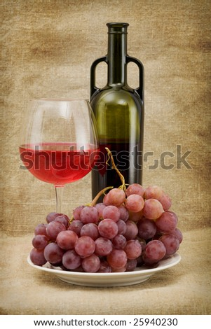 Still life with green bottle, goblet and grapes - stock photo