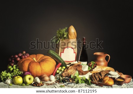 Still life with grocery bag and blank frame. Stock of food on the table with brown bag in the middle - stock photo