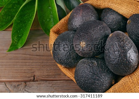 Still life  with Hass avocados in a burlap sack on a wood background with leaves. Horizontal with copy space. - stock photo