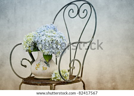 Still Life with Hortensia Flowers in old vase on retro Chair