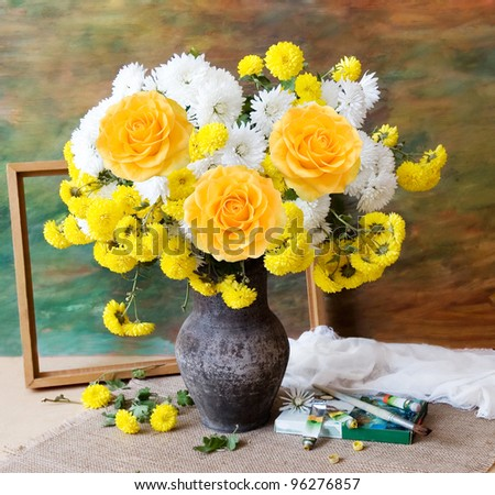 Still life with huge bunch of autumn flowers and roses, paints collection and wooden frame on painting background