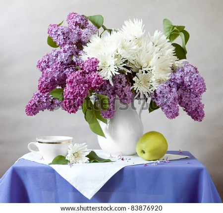Still life with huge bunch of lilac and chrysanthemums, cup and green apple - stock photo