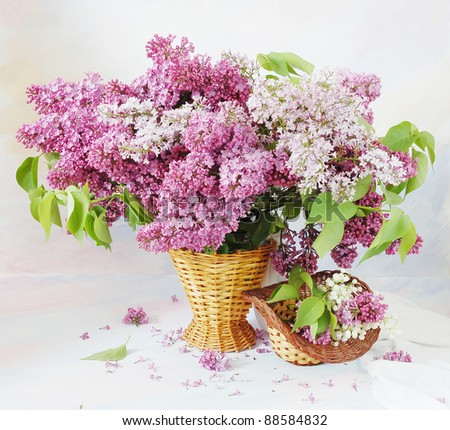 Still life with huge bunch of lilac and lily of the valley flowers on painting background - stock photo