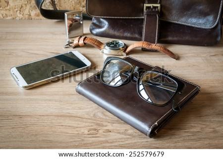 still life with leather bag, watch , lighter , glasses and smartphone on wood background - stock photo