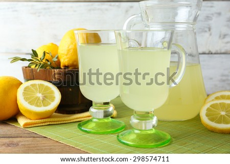 Still life with lemon juice and sliced lemons on wooden background