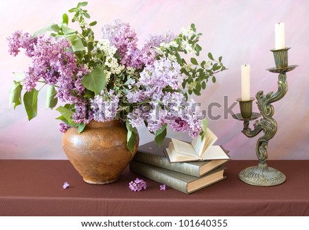Still life with lilac flowers, books pile, bronze candlestick with candles on painting background - stock photo