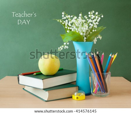 Still life with lily of valley bunch, books pile, apple and pencils on blackboard. Teacher's day concept - stock photo