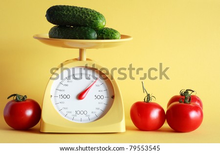 Still life with modern kitchen scale and vegetables on yellow background - stock photo