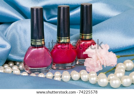 Still-life with nail polish and pearls on the blue atlas - stock photo