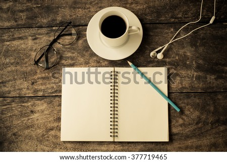 still life with notebook ,pencil, Earphone  ,glasses and cup of coffee on table - vintage filter