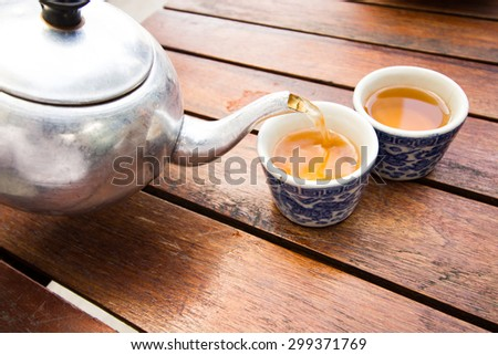 still life with old aluminum kettle and Chinese glasses tea on the wood table - stock photo