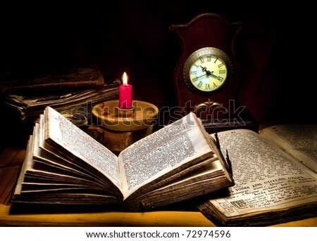 still life with old books, candle and clock - stock photo