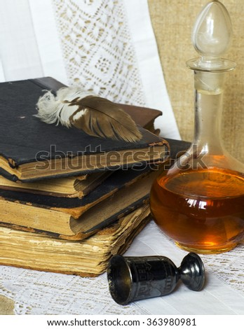 Still life with old books, feather, silver glass and brandy