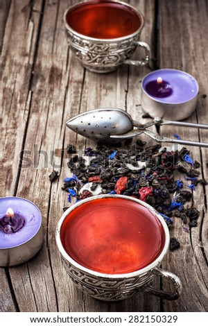 still life with old cups of brewed herbal tea and scattered welding. Photo tinted - stock photo