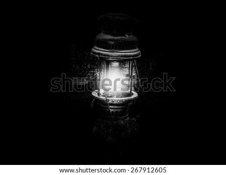 Still life with old lamp on wood,Light lamp in dark black and white photo - stock photo